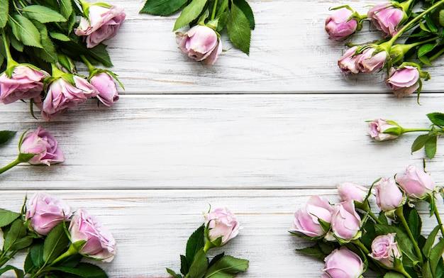 Blumen zusammensetzung. rahmen aus rosa rosenblüten auf weißem holzhintergrund. flache lage, draufsicht, kopierraum