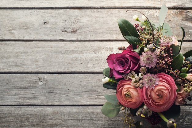 Blumenanordnung für rosen und ranunculus auf hölzernem hintergrund
