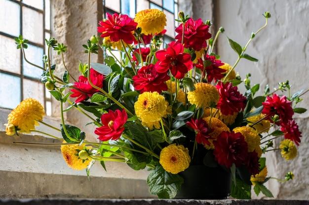 Blumenarrangement aus leuchtend roten und gelben schnittblumen dahlien