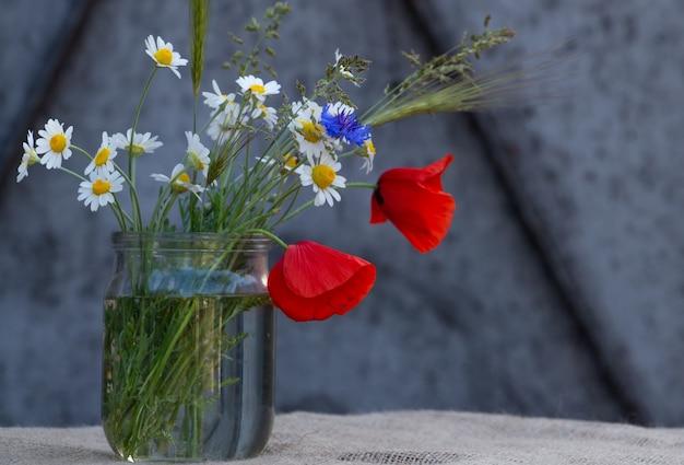 Blumenarrangement aus roten mohnblumen gänseblümchen kornblumen und wildblumen schöner feldstrauß
