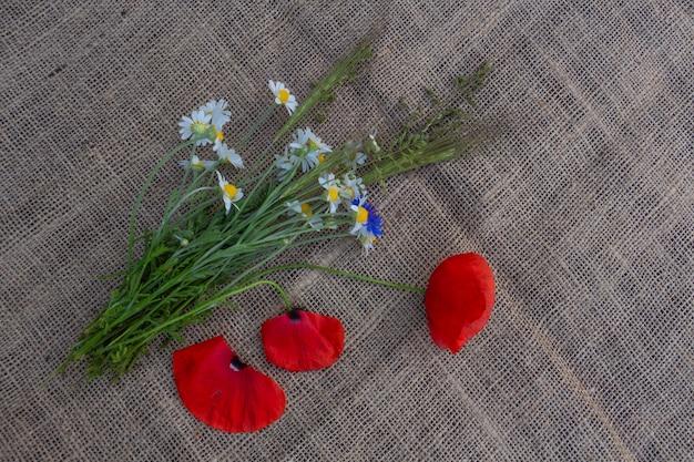 Blumenarrangement aus roten mohnblumen, kornblumen und wildblumen auf einem hintergrund von sackleinen