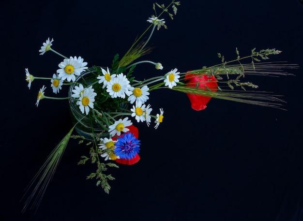 Blumenarrangement aus roten mohnblumen, kornblumen und wildblumen auf schwarzem hintergrund
