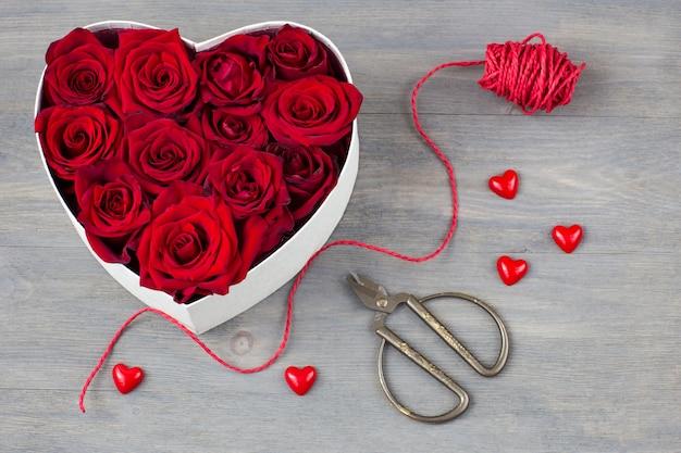 Blumenarrangement machen: schere, band, herzen, rote rosen, eine herzförmige schachtel