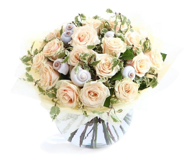 Blumenarrangement mit cremefarbenen rosen und muscheln, eine transparente glasvase. auf weißem hintergrund isoliert.