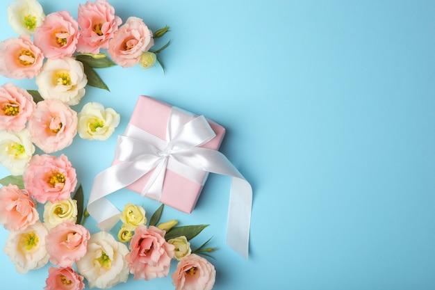Blumenarrangement und geschenk auf farbigem hintergrund draufsicht mit platz für text