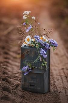 Blumenarrangement von wildblumen in einem alten briefkasten