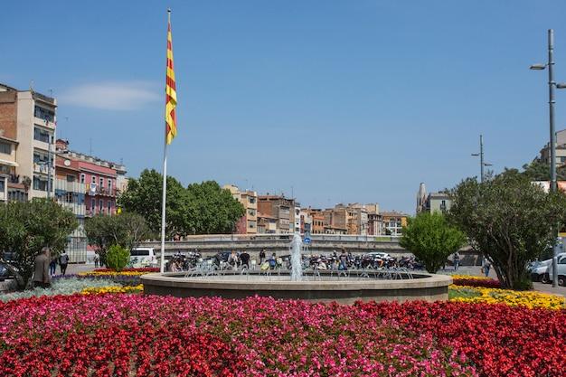 Blumenbeetbrunnen und flagge von katalonien auf placa de catalunya, girona, spanien.