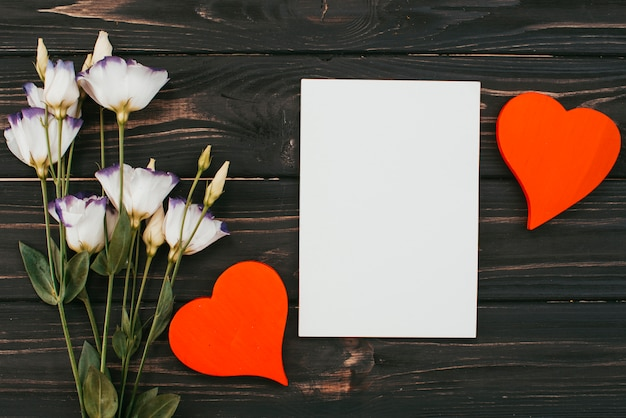 Blumenblumenstrauß mit papier und herzen auf tabelle