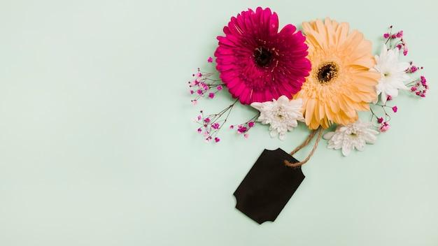Blumendekoration mit schwarzem tag auf grünem pastellhintergrund