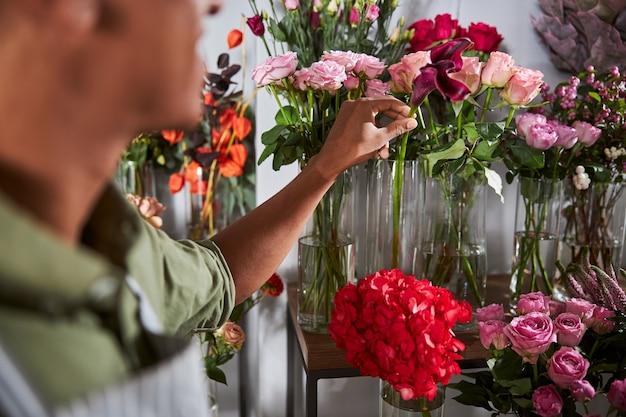 Blumendesigner, der mit blumenvasen neben dem tisch steht und eine einzelne blume aus dem wasser holt
