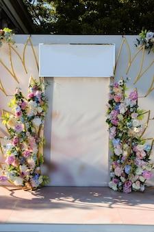 Blumenfestlicher hochzeitsbogen mit leerem schild für glückwunschtext. für besondere anlässe