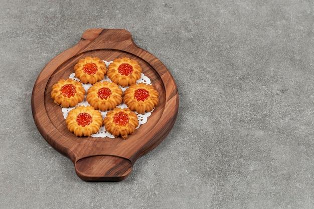 Blumenförmige kekse mit gelee auf holzbrett