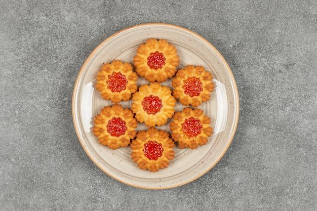 Blumenförmige kekse mit gelee auf keramikplatte