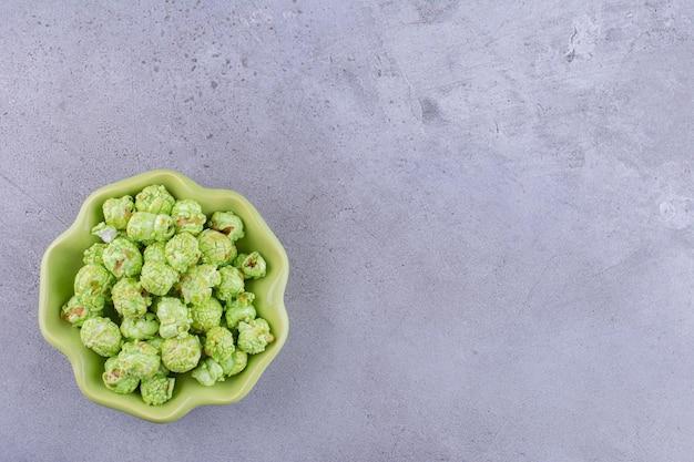 Blumenförmige schüssel mit einem bescheidenen haufen von mit süßigkeiten überzogenem popcorn auf marmorhintergrund. foto in hoher qualität