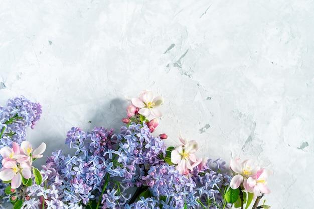 Blumenfrühlingshintergrund mit der vielzahl von bunten apfel- und fliederblumen auf grauem betonhintergrund, draufsicht, platz für text.