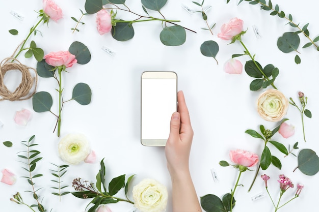 Blumengesteck mit einem handy in einem blumenrahmen, in einer draufsicht und in einer ebenenlage