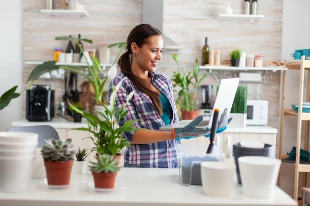 Blumenhändler, der laptop in der küche hält, während er blumen für die dekoration mit fruchtbarem boden herstellt