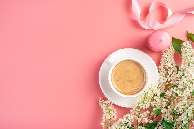 Blumenhintergrund mit cappuccino-tasse und kerzen auf rosa hintergrund. ansicht von oben, kopienraum.