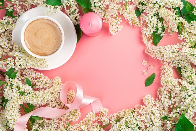 Blumenhintergrund mit kaffeetasse, kerzen und band auf rosa hintergrund. platz kopieren.