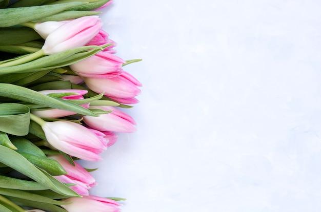 Blumenhintergrund mit tulpen blüht auf blauem abstraktem hintergrund.