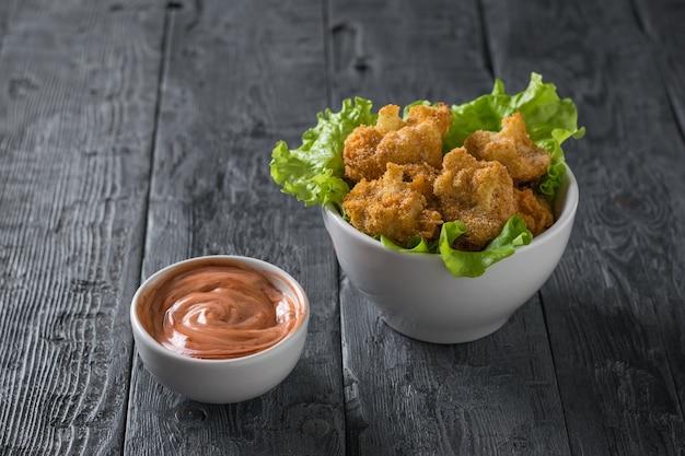 Blumenkohl mit salat und sauce auf einem holztisch geschlagen. vegetarische blumenkohl vorspeise.