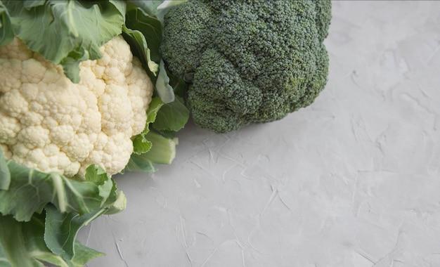 Blumenkohl- und brokkolikopfnahaufnahme auf konkreter tabelle. gemüse auf dem tisch. exemplar