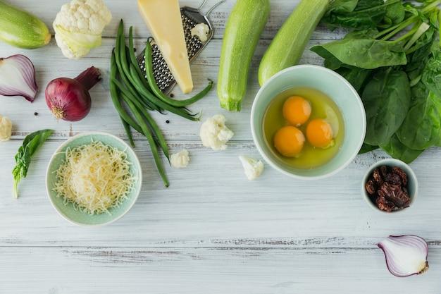 Blumenkohl, zucchini, rote zwiebel, grüne bohnen, eier, käse und spinatblätter für die herstellung von vegetarischer frittata
