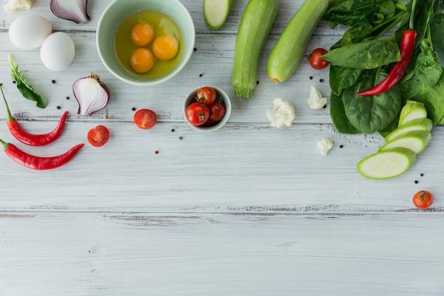 Blumenkohl, zucchini, zwiebel, grüne bohnen, eier, tomaten, chili und spinatblätter für die herstellung von vegetarischer frittata