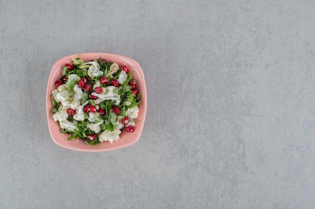 Blumenkohlsalat mit kräutern und granatapfelkernen.
