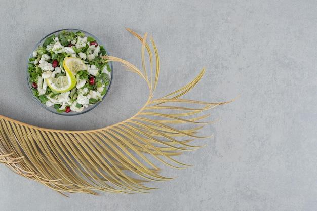Blumenkohlsalat mit roten granatapfelkernen in einem teller.