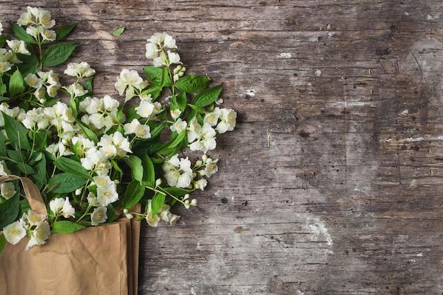 Blumenkomposition für valentinstag, muttertag oder frauentag. jasmin frühlingsblumen auf altem holz