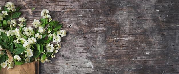 Blumenkomposition für valentinstag, muttertag oder frauentag. jasminblüten auf vintage-holz