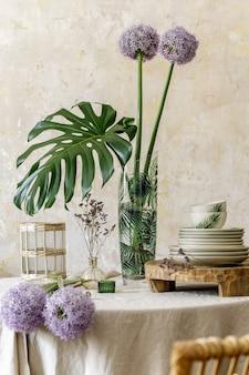 Blumenkomposition im kücheninnenraum mit hölzernem familientisch, schönen blumen in vase, tellern, tassen, tablett und eleganter dekoration. esszimmer in moderner wohnkultur..