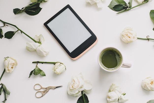 Blumenkomposition mit digitaler tablette, weiße rosen auf weißem hintergrund. flach, ansicht von oben