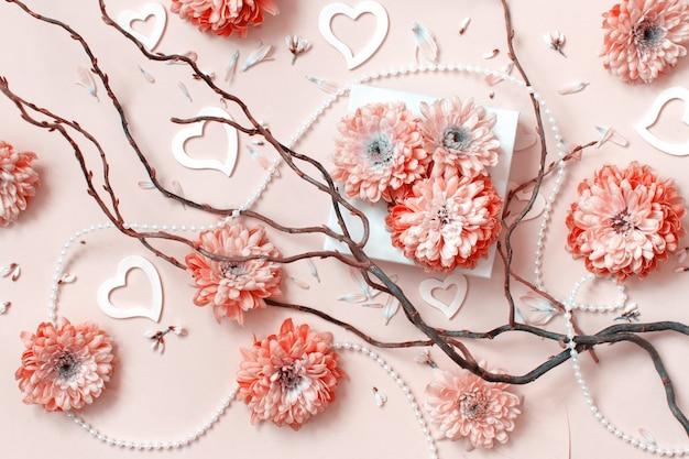 Blumenkomposition mit herzen auf einem pastellrosa hintergrund