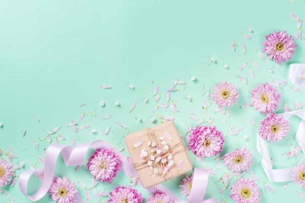 Blumenkomposition mit herzen und geschenkbox auf pastell