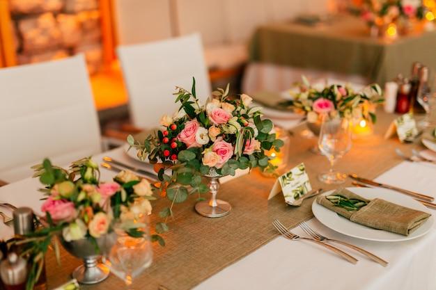 Blumenkompositionen auf dem hochzeitstisch in hochzeitsdekorationen im rustikalen stil