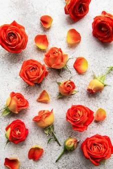 Blumenkompositionsrahmen aus roten rosen und blättern auf betonhintergrund
