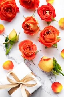 Blumenkompositionsrahmen aus roten rosen und blütenblättern und geschenkboxraum