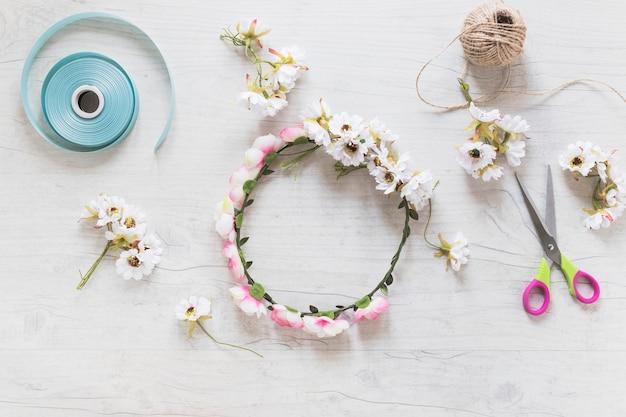 Blumenkranz mit band; schnurspule und -schere auf weißem strukturiertem hintergrund
