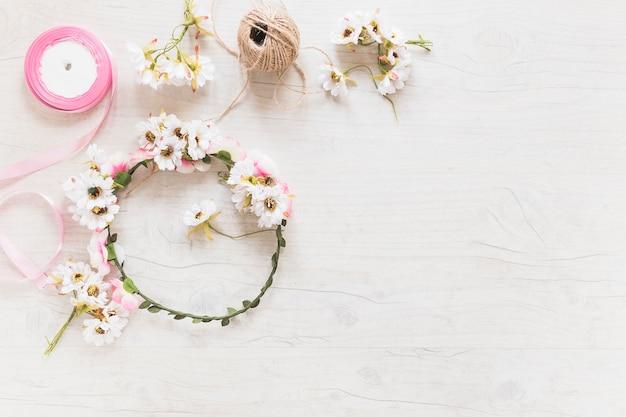 Blumenkranz; schnurspule und rosa band auf strukturiertem hintergrund