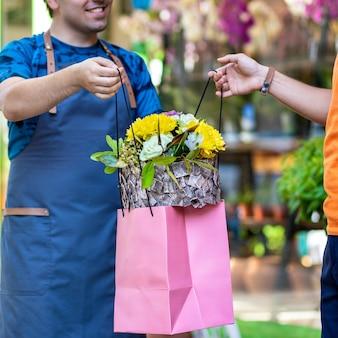 Blumenladenarbeiter, florist, der dem kunden eine blumenboutique gibt