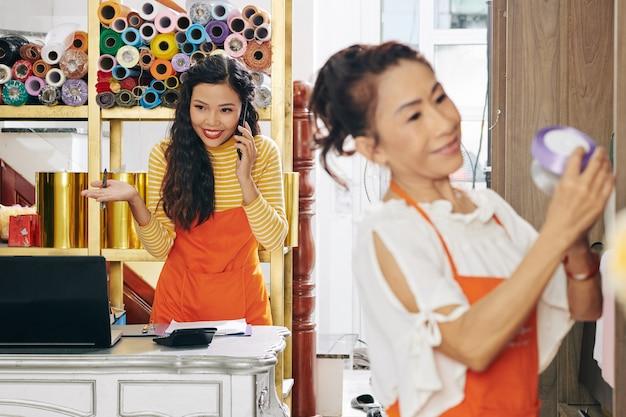 Blumenladenbesitzer telefoniert mit dem kunden, wenn ihre mitarbeiterin ein satinband für einen blumenstrauß auswählt