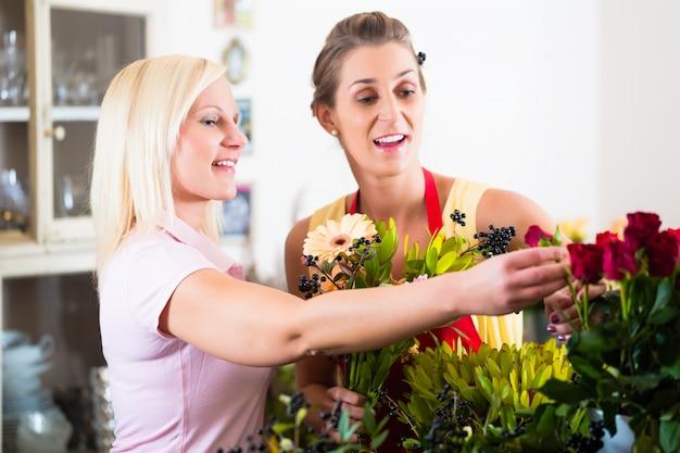 Blumenladenverkaufsfrau, die dem kunden rat gibt