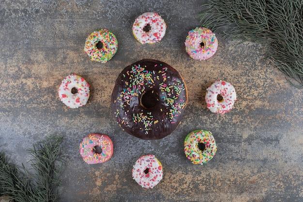 Blumenmotiv mit donuts zwischen zypressenzweigen auf holzoberfläche angeordnet