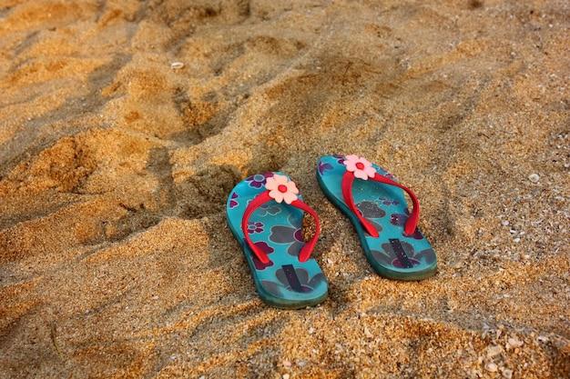 Blumenmuster auf bule sandalen auf strand.