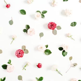 Blumenmuster aus roten und beige rosen, grünen blättern, zweigen auf weißem hintergrund. flache lage, ansicht von oben