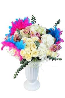 Blumenmuster mit cremefarbenen rosen, weißen blumen und mehrfarbig bemalten federn in weißer plastikvase, lokalisiert auf weißem hintergrund.