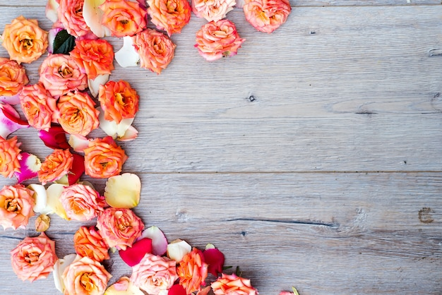 Blumenmuster, rahmen gemacht von den rosen auf hölzernem hintergrund. flache lage, draufsicht.