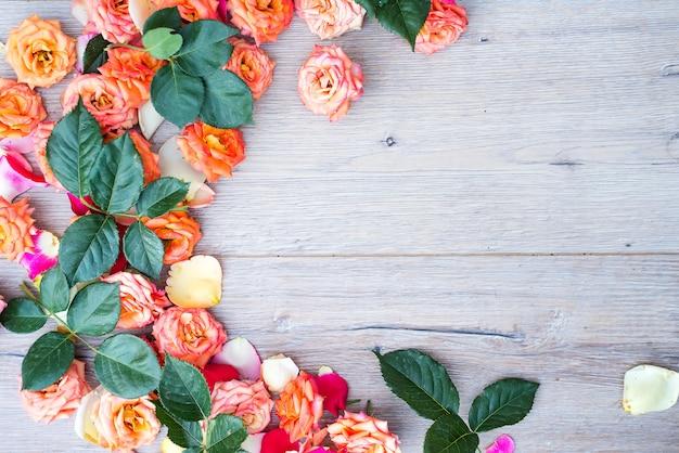 Blumenmuster, rahmen gemacht von den rosen auf hölzernem hintergrund.